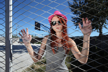 teenager clings to the metal mesh of the playground