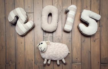 Happy New year 2015 and toy sheep handmade wooden background