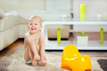 Smiling baby sitting on chamber pot