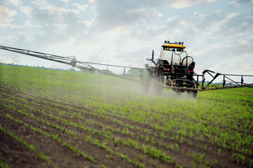 farm tractor spraying substances against pests in the field
