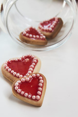 Red hearts cookies on white background and a bowl