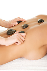 Young attractive woman getting hot stone massage