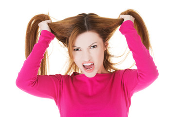 Frustrated and angry woman pulling her hair