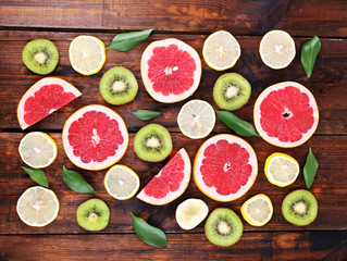 Ripe slices lemon, kiwi and grapefruit on wooden background