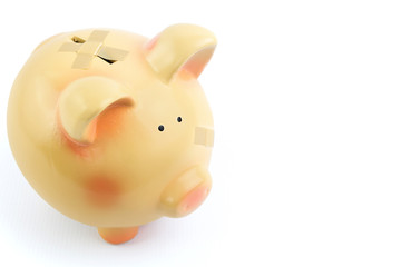 Piggy bank with medical patches, isolated on white background