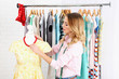 canvas print picture - Beautiful young stylist near rack with hangers