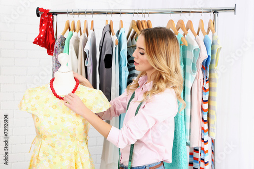 canvas print picture Beautiful young stylist near rack with hangers