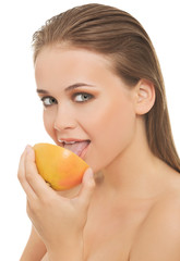 Young nude woman eating grapefruit