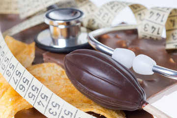 Schokolade mit einem Bandmaß und Stethoskop