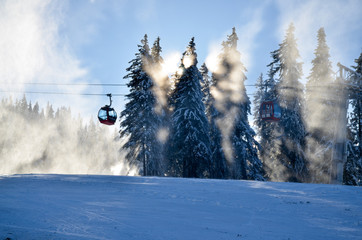 Cable car on ski lope, landscape with snow on trees and sunlight