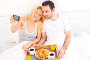 Young attractive couple taking selfie during breakfast