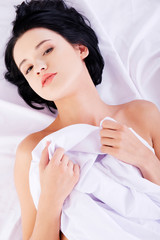 Beautiful woman relaxing in bed with soft quilt