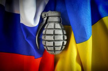 Zerknüllte Fahnen von Russland und der Ukraine mit Handgranate