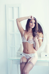Beautiful alluring young woman in white sexy lingerie