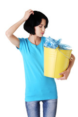 Pensive woman holding bucket of plastic rubbish