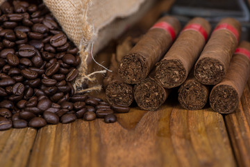 Cuban cigars and rust coffee beans on wood
