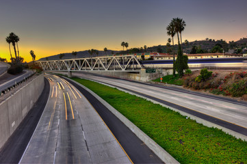 Freeway, trestle, and train all converging on the sunset