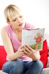 Pretty blonde woman reading a newspaper
