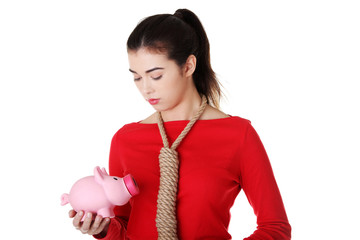 Sad woman with piggybank and rope around neck