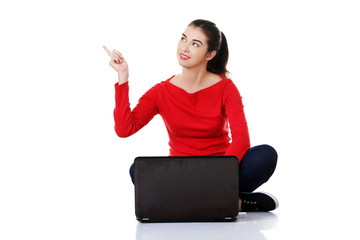 Woman sitting cross-legged pointing up