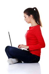 Side view woman sitting cross-legged with laptop