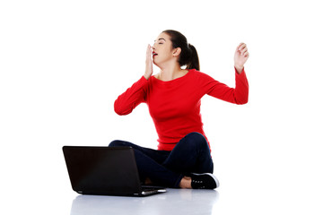 Tired woman sitting cross-legged with laptop