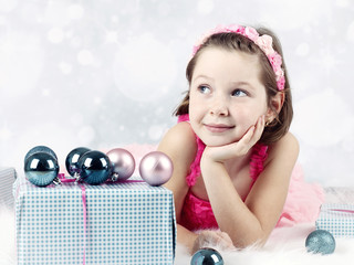 Little girl lying on the floor with christmas balls and presents