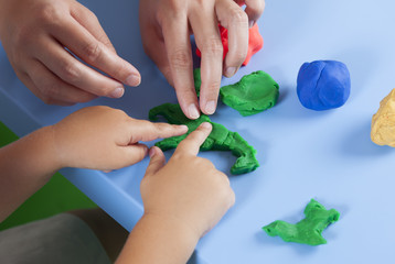 Child and mother playing with playdough