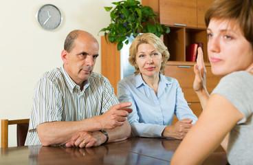 Parents scolding adult daughter