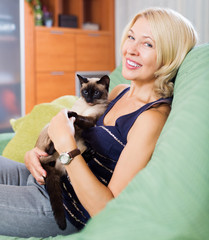 Woman sitting on sofa with her cat