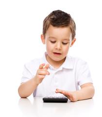 Cute boy is using calculator