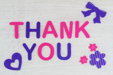 Thank you written with colorful letters on white wood