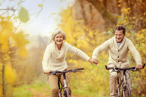 Active seniors riding bike - 73938363