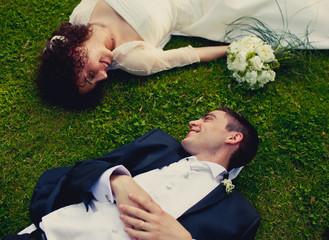 Sposi sdraiati su prato verde