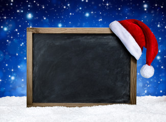 blackboard with santa hat on snow