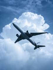 Passenger airplane flying in the sky processed in blue