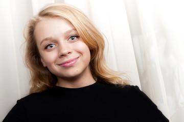 Smiling blond Caucasian girl studio portrait
