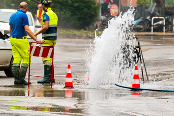 road spurt water beside traffic cones and two technicians