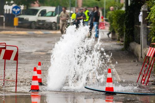 road spurt water beside traffic cones - 73940912