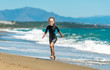 canvas print picture - girl in a wetsuit running along the beach
