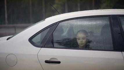 Child female in the car in raining