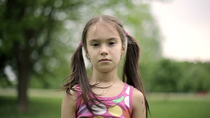Portrait girl is angry in a summer park in slow motion