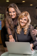 Two smiling women looking a laptop and smiling.