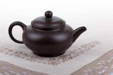 Traditional asian clay teapot with lace doily.