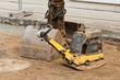 Ein Sandrüttler steht neben einer Bagger-Doppelschaufel