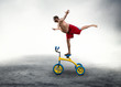 Man standing on a small bicycle - 73945977