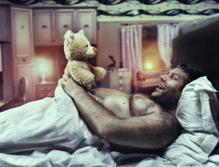 Adult man in bed looks at toy bear