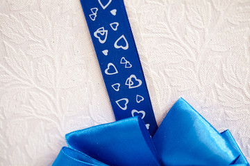 blue ribbon with hearts on a light background