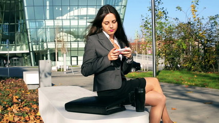 Happy businesswoman sitting outside the building and texting