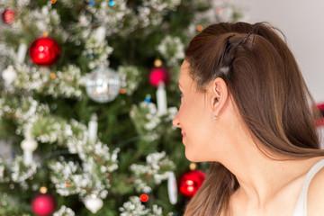 Beautiful woman posing next to Christmas tree